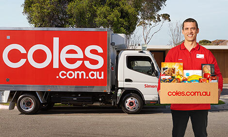 Coles truck with delivery man holding box of groceries