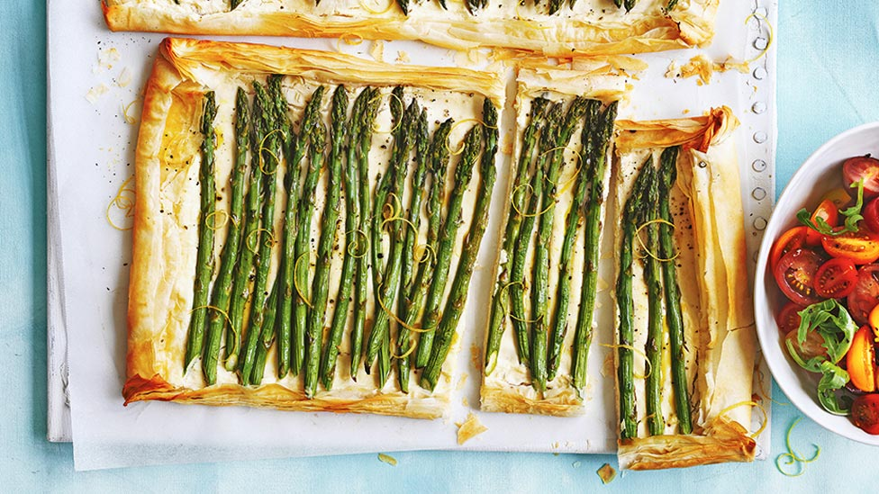Ricotta and asparagus tarts cut in large pieces, served with tomato and rocket leaves